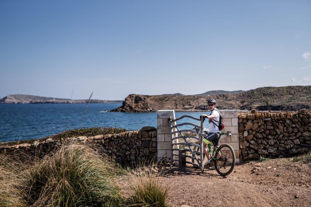 Un ciclista obrint una de les moltes barreres que hi ha al Camí de Cavalls (Foto: Jordi Saragossa).